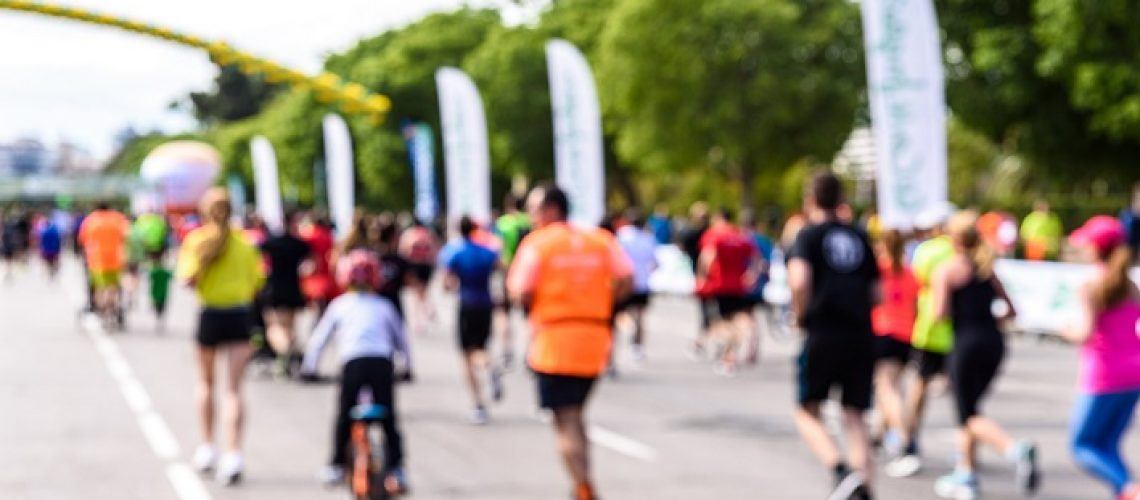 Unfocused scene of runners of a popular race with children and seniors doing jogging exercise.